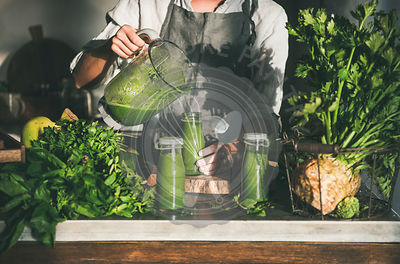 Woman in apron pouring green smoothie from blender to bottle