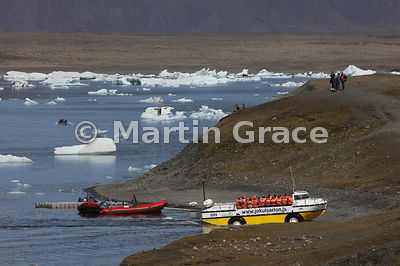 Amphibious vehicle full of tourists leaving the water at Jokulsarlon glacier lagoon, Austurland (Eastern Region, East Iceland...