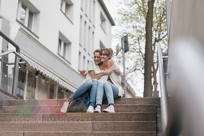 Friends sitting on stairs in the city, sharing cardigan