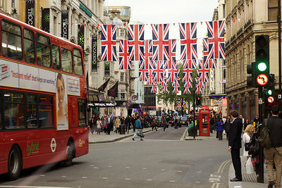 Union Flags hang in Leicester Square as a Red Bus approaches
