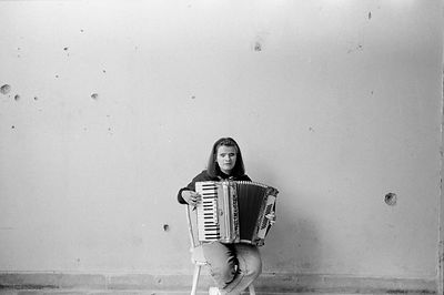 A girl practices her accordian in the ruins of the Blind School