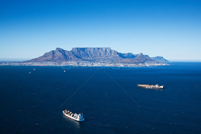 Aerial photograph of container ship with Cape Town in the distance, Atlantic Ocean, South Africa, Western Cape Province, Marc...