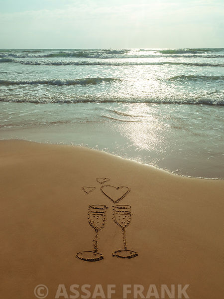 Wine glasses with heart drawn in sand on the beach