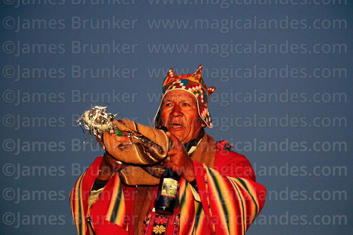 Aymara shaman or amauta carrying a decorated llama foetus offering at start of Aymara New Year celebrations, Tiwanaku, Bolivia