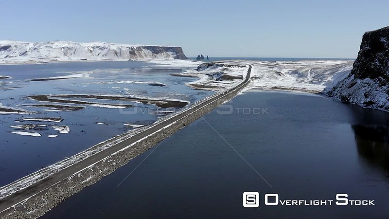 Cars Driving Along a Narrow Road Crossing a Lake in Iceland