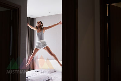 Excited woman wearing headphones jumping in bed