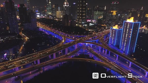 Elevated Road Overpass at Night with Blue Illumination and Shanghai Cityscape. China. Aerial View. Drone is Flying Upward, Ca...