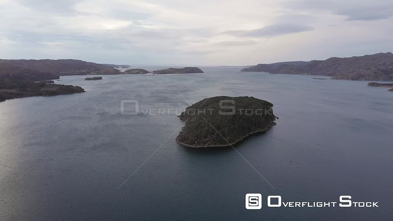 Aerial drone shot of a small uninhabited island on a loch (lake) in Highlands of Scotland