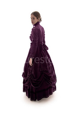 A Victorian woman, in a purple, dress, looking away – shot from eye level.