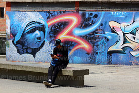 Young man surfing internet on mobile phone in public wifi area in Plaza Camacho, La Paz, Bolivia