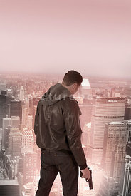 An atmospheric image of a lone mystery man standing on top of a tall building, with a gun, in New York City.