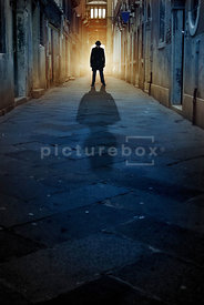 An atmospheric image of a mystery man standing in a narrow street in Venice, at dawn.