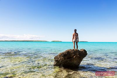 Tourist on a rock looking at the sea, Aitutaki, Cook Islands