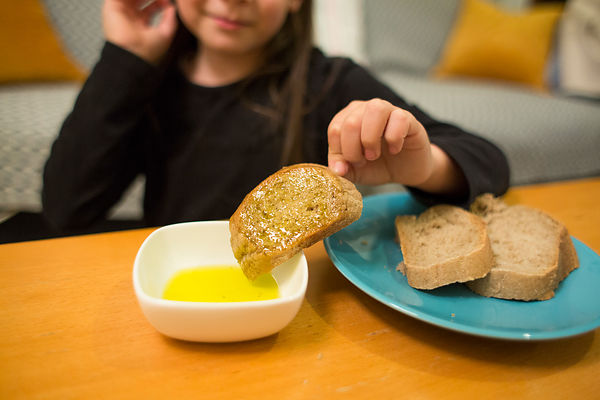 Alessandra, 7 ans, trempe son pain dans de l'huile d'olive, Crète, Grèce / Alessandra, 7, dipping her bread in olive oil, Cre...