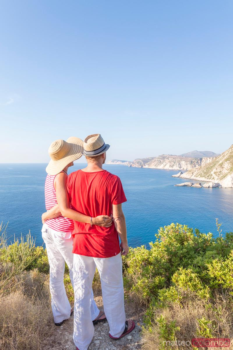 Couple looking at the coastline from lookout. Kefalonia, Greek Islands, Greece