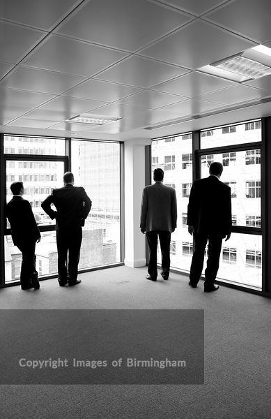 Business men looking out of an office window, Birmingham, England.