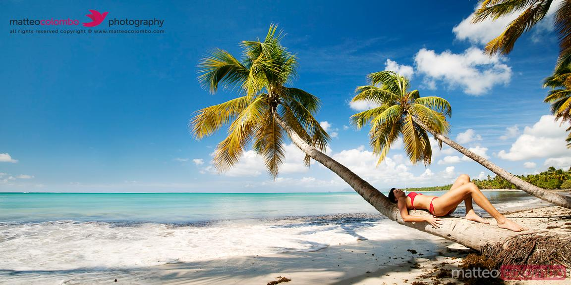 Woman in red bikini relaxing on palm tree in the Caribbean