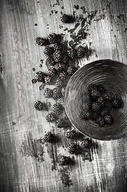 Organic ripe blackberries in a black wire bowl on a wooden surface.