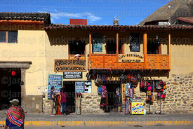 Tourists looking at menu outside restaurant and craft shop, Ollantaytambo, Sacred Valley, Peru