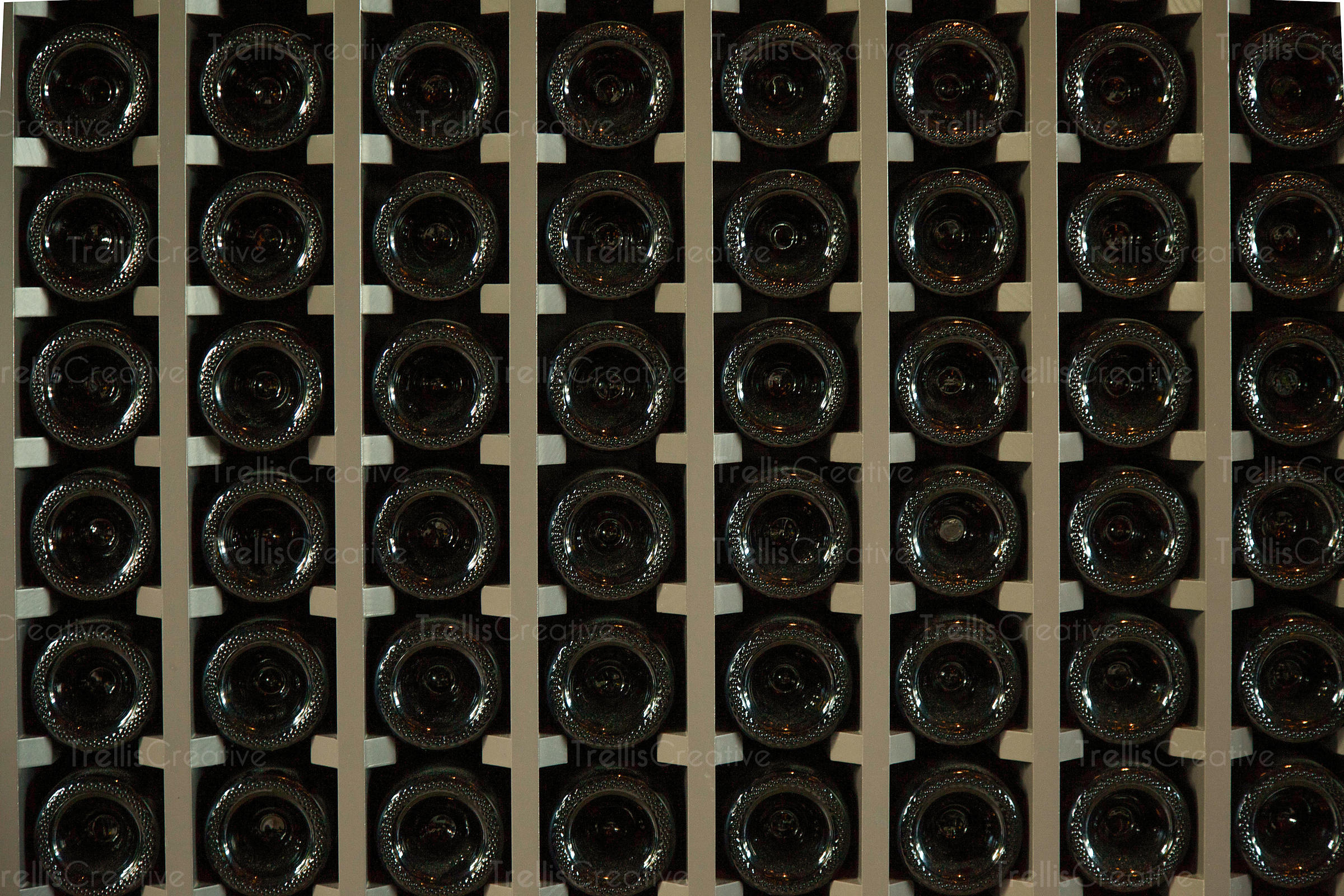 A rack of many bottles of red wine ageing in a cellar