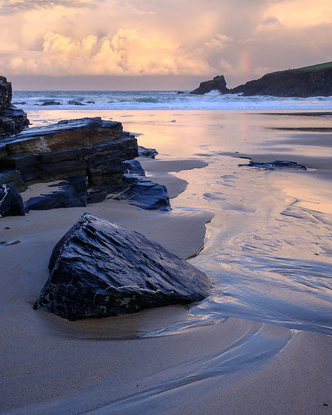 Atlantic clouds reflect dawn light onto the wet sands and rocks of Trevone, near Padstow in Cornwall, UK