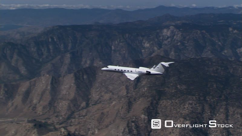 Air-to-air side view of executive jet over rugged terrain