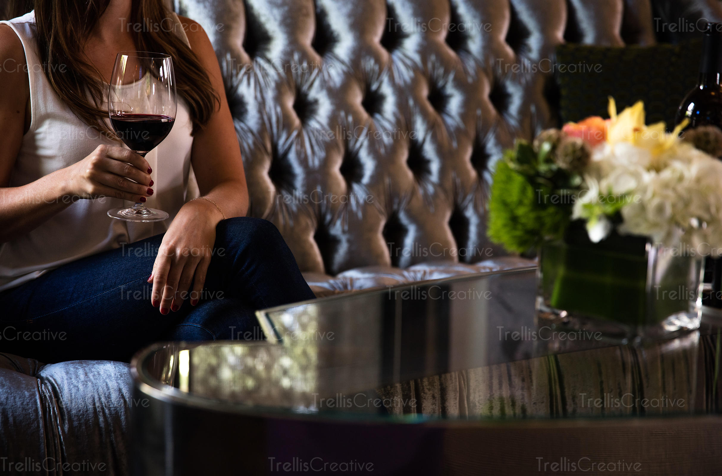 Close-up of a woman sitting on couch holding a glass of red wine in her hand