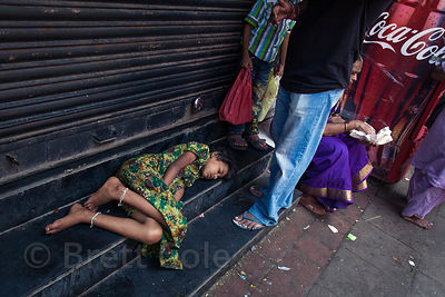 A girl sleeps on a bench in Lalbaug, Mumbai, India.