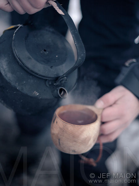 Pouring tea into wooden cup