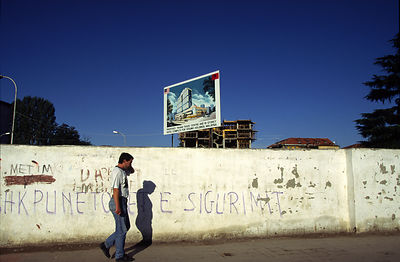A man walks past a site with a poster for a new development, Tirana