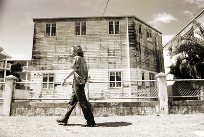 An atmospheric image of a mystery man walking past an old, wooden derelict house.