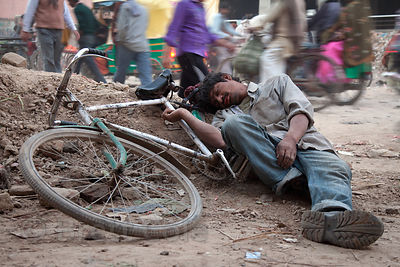 A drunk man lies passed out on the side of the road with his bicycle, near Assi Ghat, Varanasi, India.