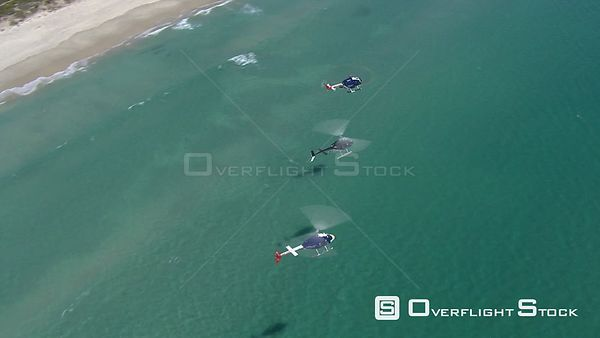 Aerial of three helicopters flying over the ocean towards Cape Town. Cape Town Western Cape South Africa
