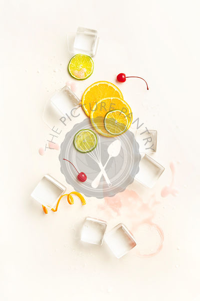 Overhead layout of minimal cocktail ingredients including large ice cubes, orange and lime wheels, twists and cherries on pal...