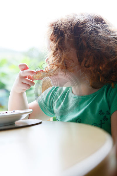 A little girl eating toast