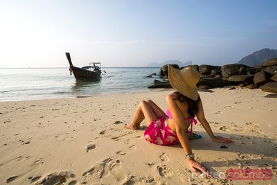 Woman enjoying sunrise on tropical beach, Thailand