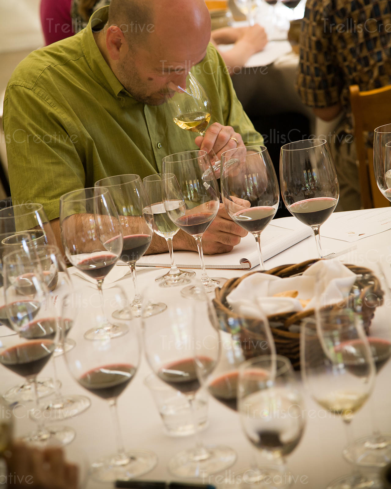 Man in green shirt tasting red wines has nose in glass, making notes, surrounded by glasses.