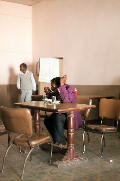 India - Allahabad - A man eats whilst another washes his hands  in the Indian Coffee House