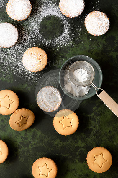 Festive fruit mince pies being dusted with icing sugar.