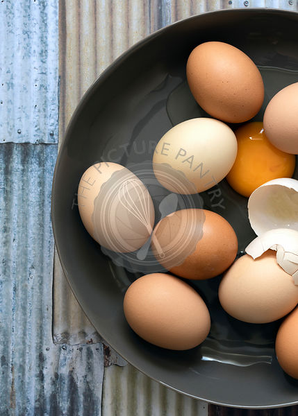 A broken egg in a bowl of eggs.