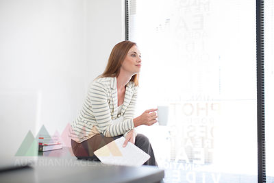 Businesswoman in office holding cup of coffee