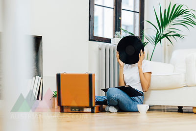 Young woman sitting on grounf listening music from record player, hiding behind vinyl