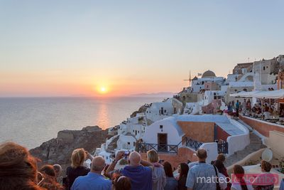 Tourists admiring sunset on the island of Santorini, Greece