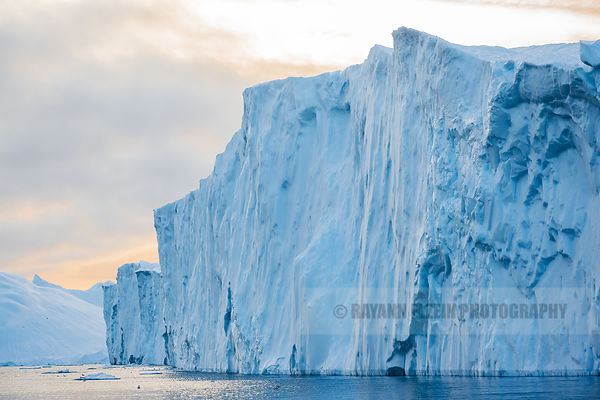 Large iceberg with vertical walls in golden evening light in Ilulissat Icefjord in Greenland