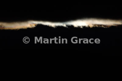Abstract formed by the brilliantly lit edge of a cloud creeping over the ridge of a hill, Glen Feshie, Scottish Highlands