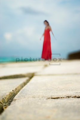 An atmospheric image of a blurred woman on a jetty, in the Maldives.
