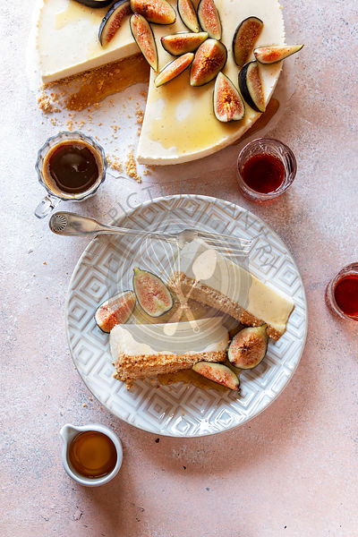 Ricotta cheesecake on the plate topped with fresh figs and drizzled with maple syrup