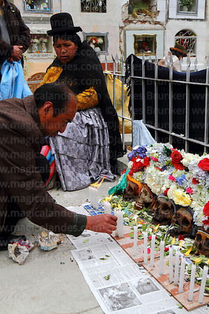 Devotee offering candles to skulls in cemetery, Ñatitas festival, La Paz, Bolivia