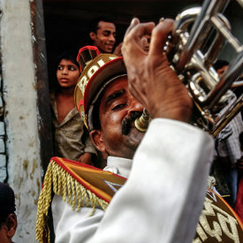 Band member blows his trumpet during a street party in Kathputli
