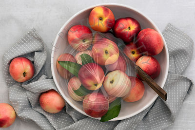Red and yellow nectarines in a bowl with a knife.